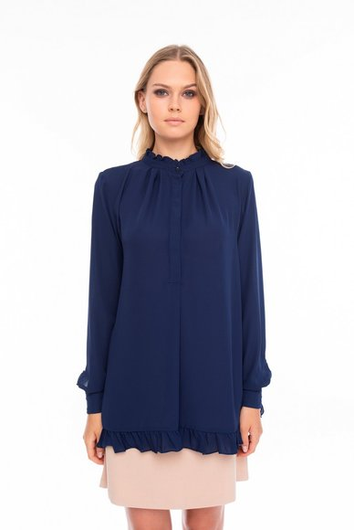 An elongated blue blouse, with a cut on the back
